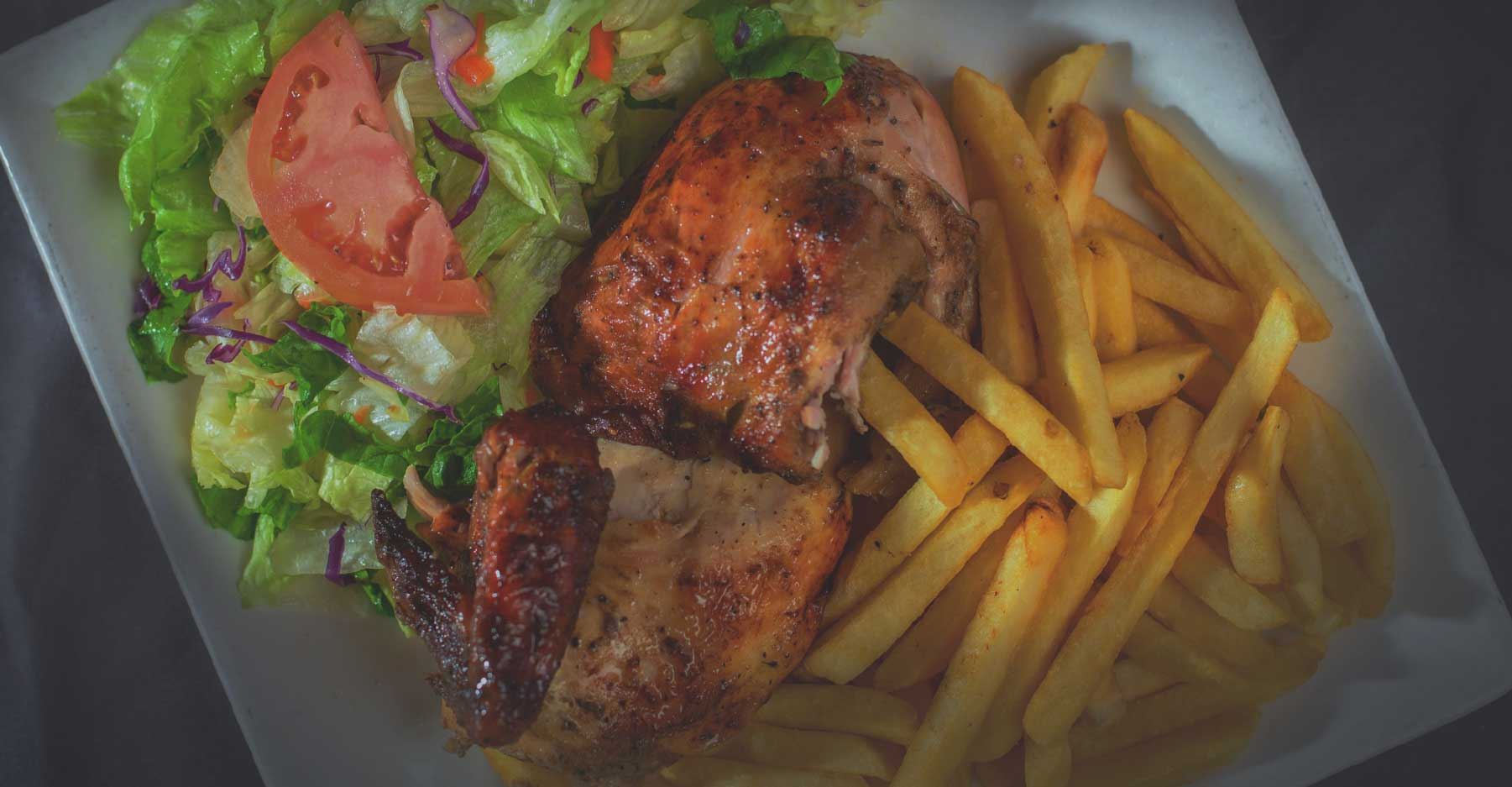 plate of chicken with fries and salad